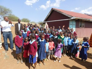 Ellen B. with the students at Kimelok school, in front of the 30,000 L rainwater harvesting tank. Even though it is the dry season, enough rain has fallen since the tank was built that they will have sufficient drinking water and handwashing water to last until the rains come in May.